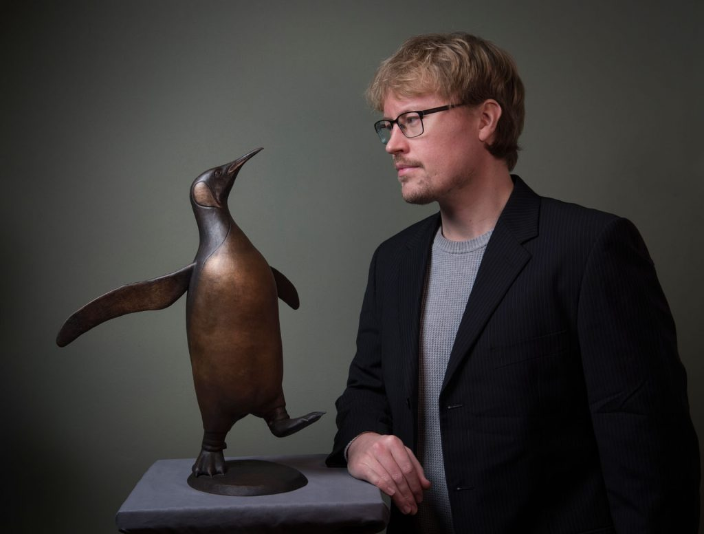 Artist Anthony Smith with his bronze sculpture of a King Penguin (Medium)