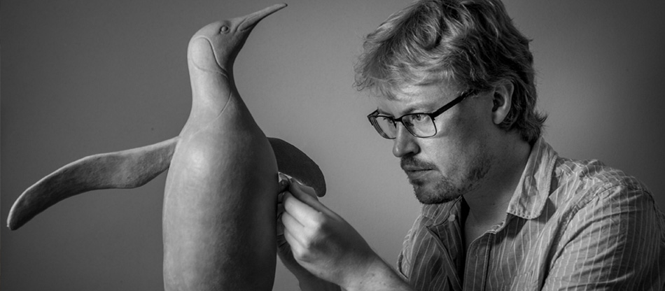 Artist Anthony Smith sculpting a King Penguin in his studio